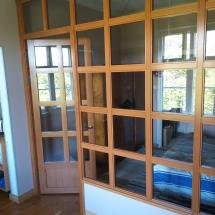 Puurunkoinen lasiseinä ja -ovi sekä kipsilevyseinäkaistaleet ylös ja alas